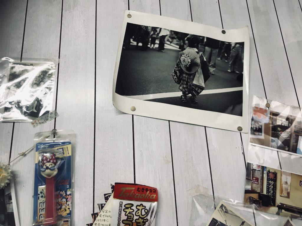 白い壁に掛けられた写真や駄菓子等