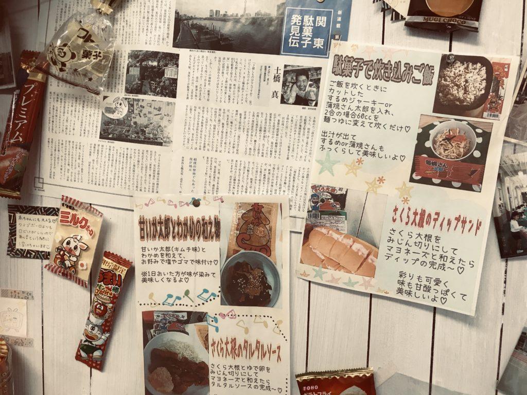 壁に掛けられた様々な紙と駄菓子