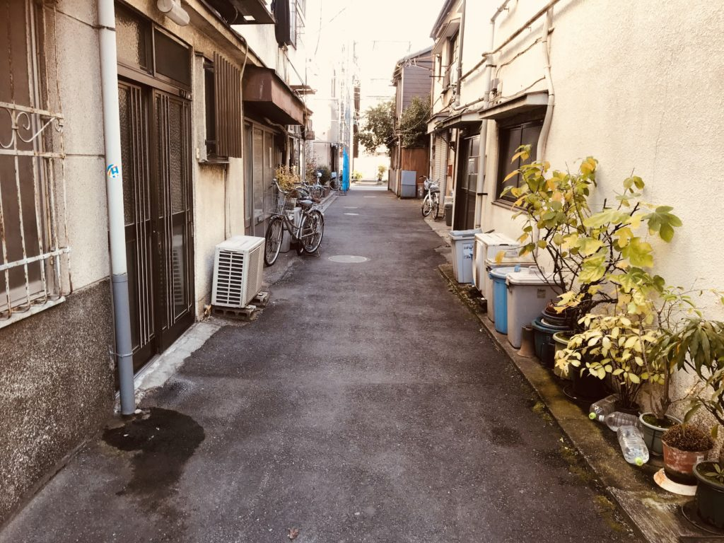 自転車や植物が置かれた狭い路地裏