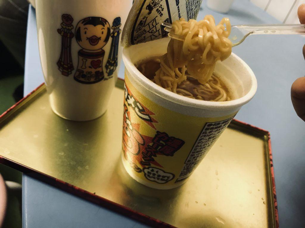 テーブルに置かれたコップと食べられようとしているブタメン
