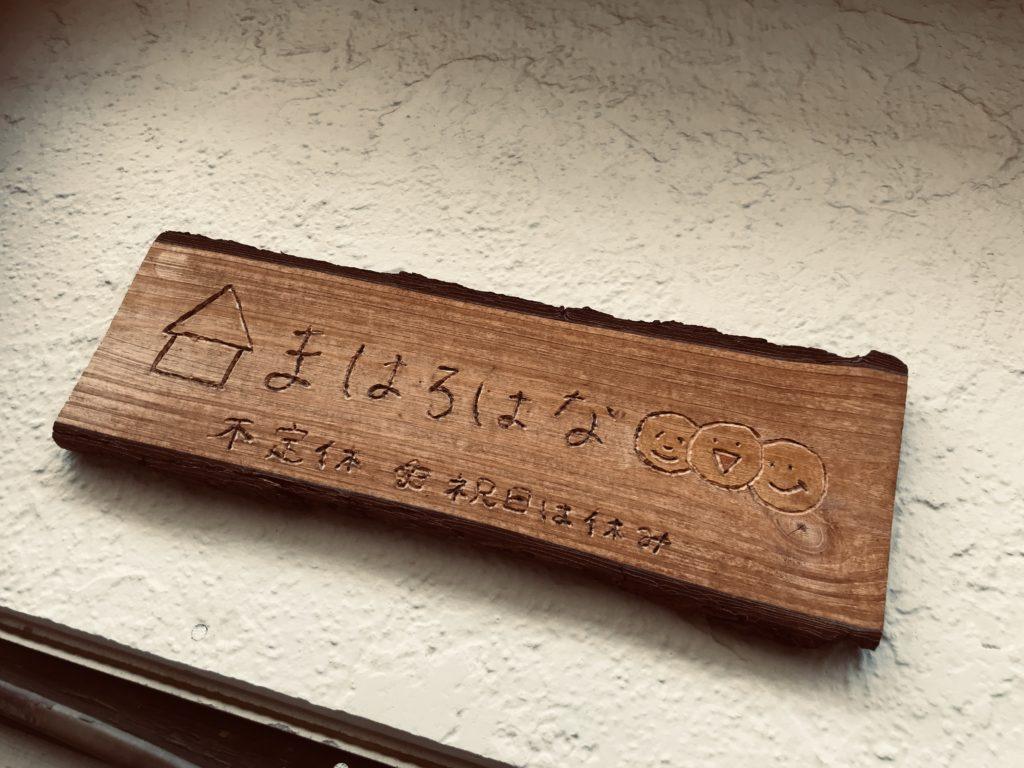 駄菓子屋さんの名前と不定休と書かれた木の看板