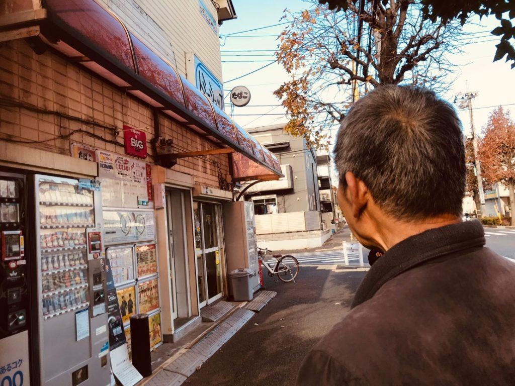 自販機が並んだお店を眺める男性