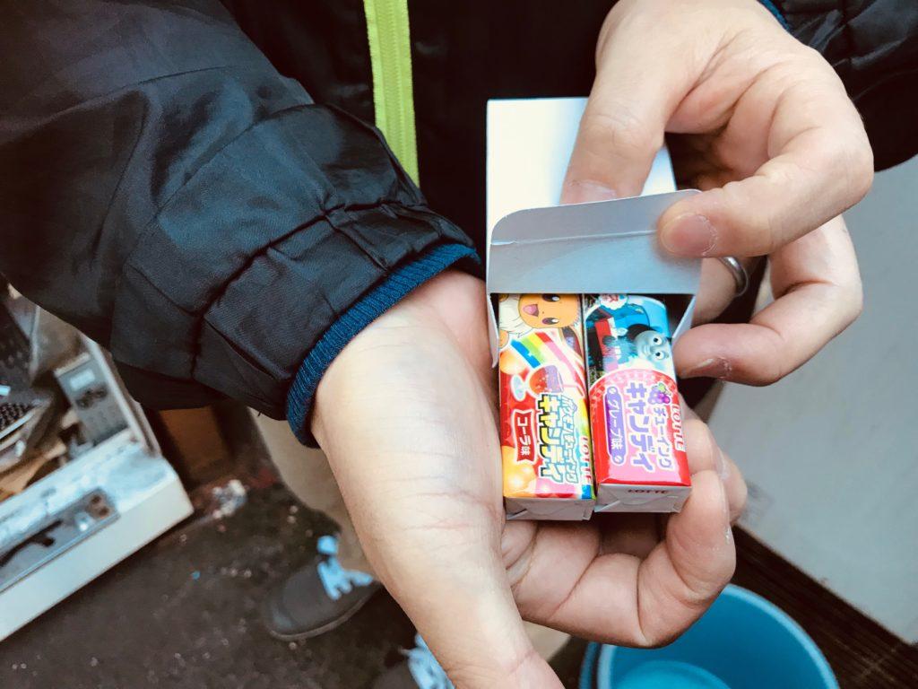 箱に入った駄菓子を持つ男性の手
