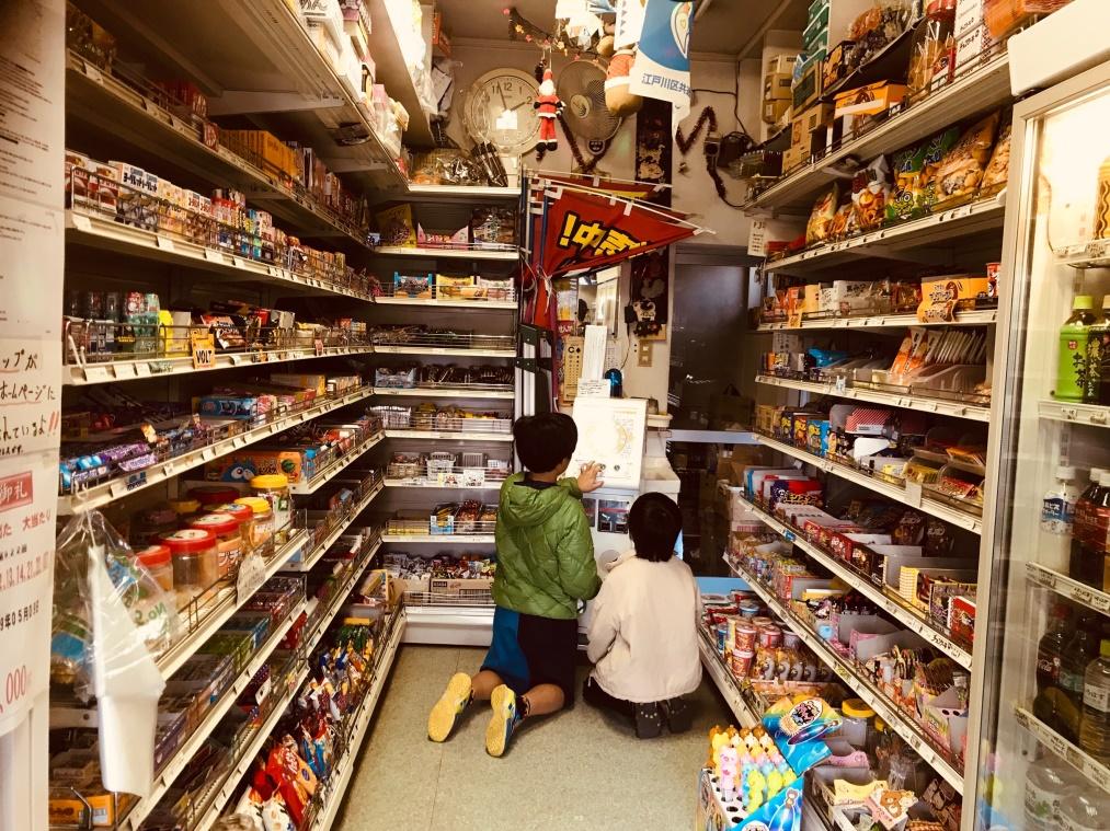 広い駄菓子のスペースで駄菓子を選ぶ二人の子ども