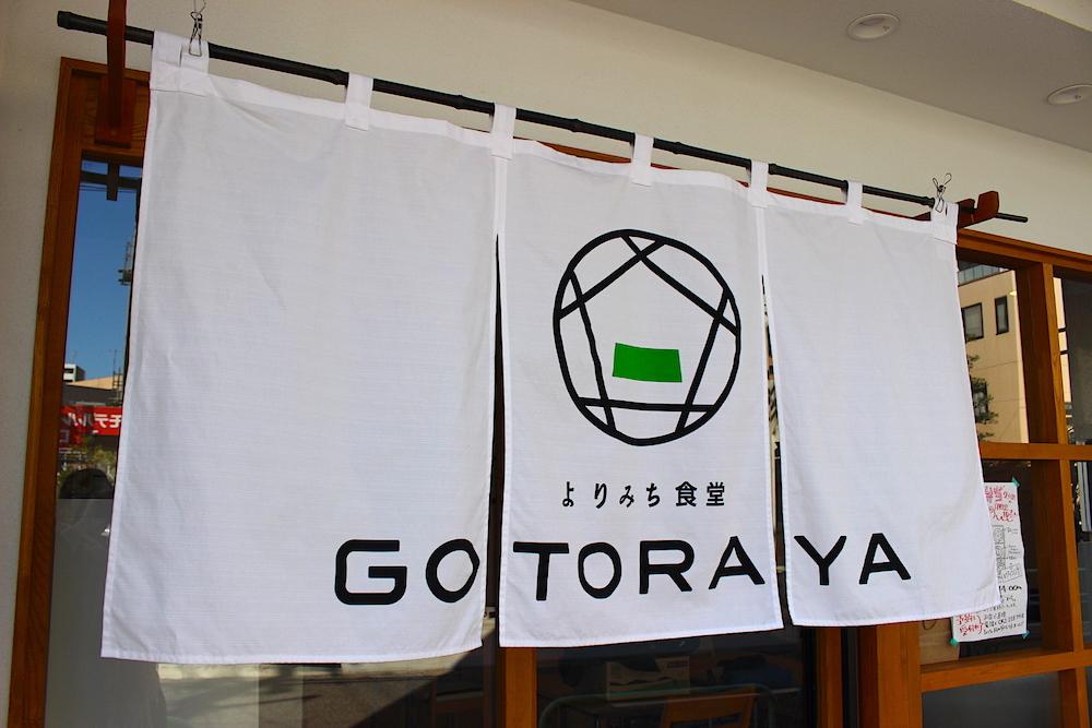 お店の名前とロゴが書かれた白い暖簾