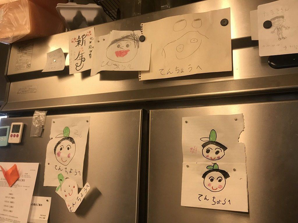 子ども達の描いた似顔絵が貼られた冷蔵庫