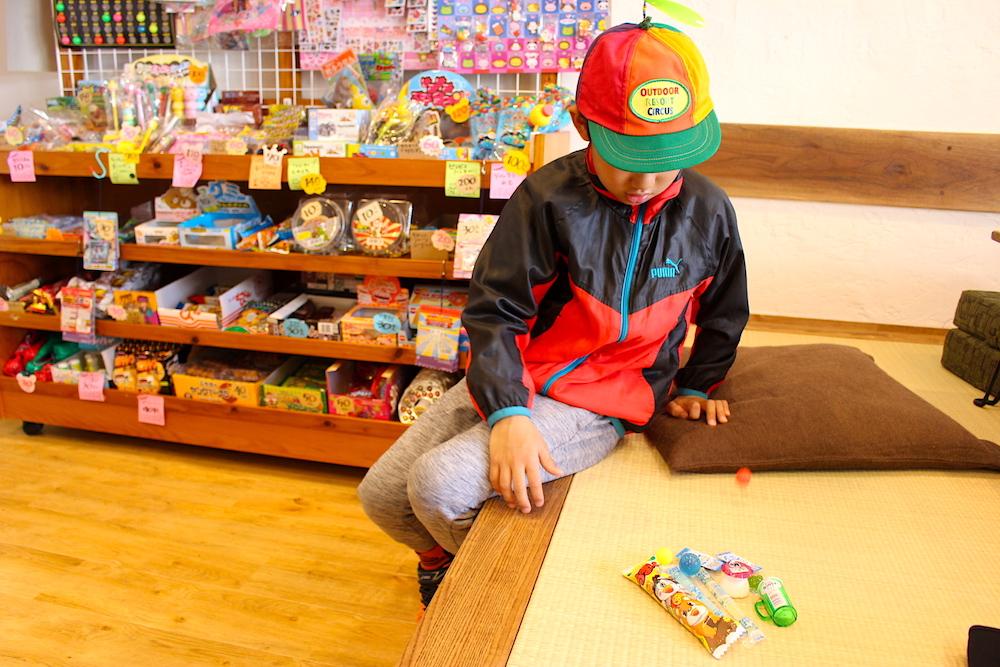 畳に座って駄菓子を見つめる男の子