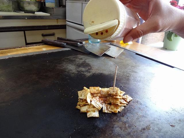 鉄板焼きに置かれた白い駄菓子と七味唐辛子