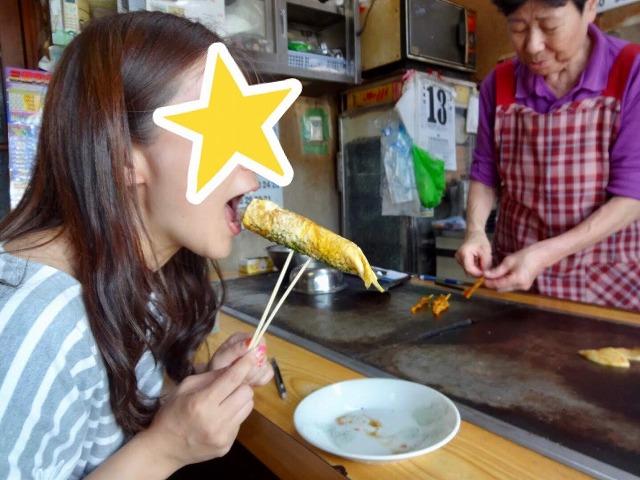 卵焼きを食べる女性と奥に立つ女性