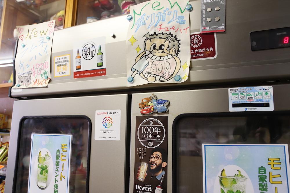 手描きのイラストが貼られた大きな冷蔵庫