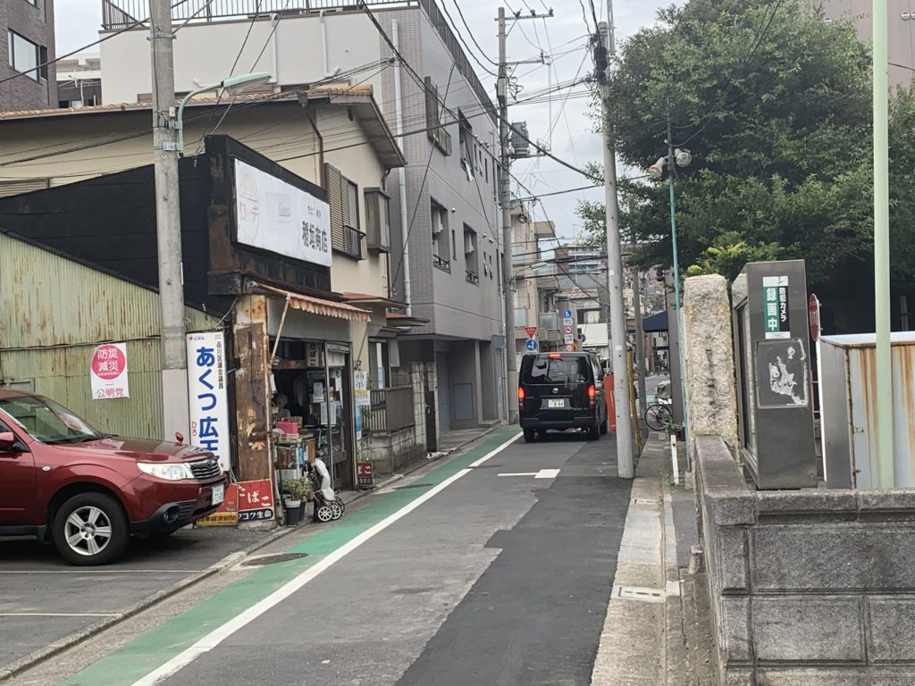道路に止められた車と店の入り口