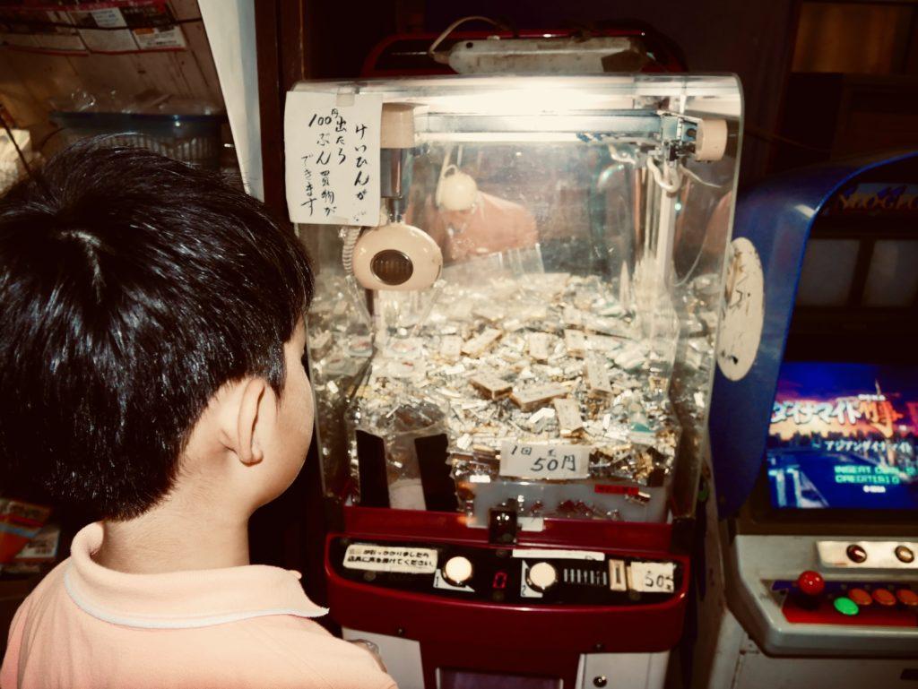 クレーンゲームを見つめる少年