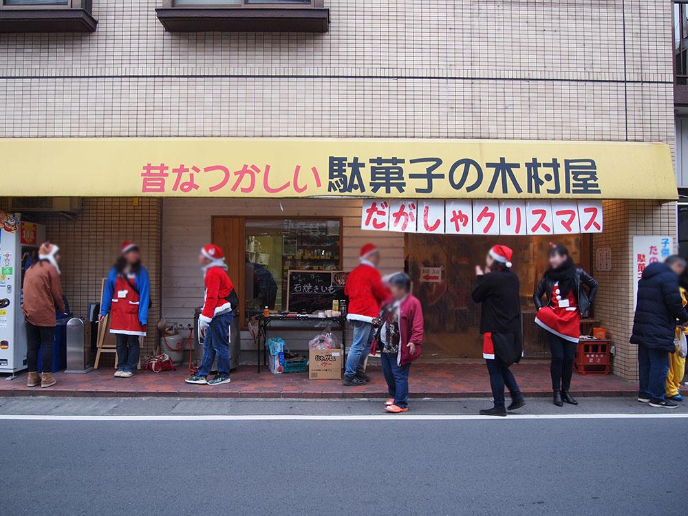 サンタの格好をしてお店の前に立つ人々