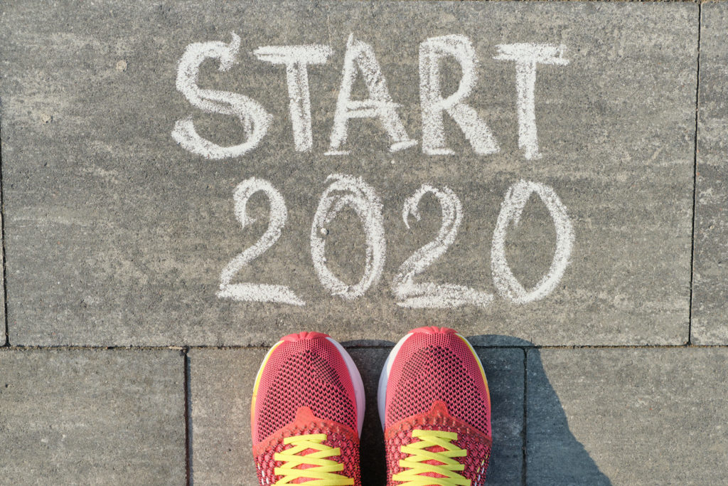 Start 2020, text on gray sidewalk with woman legs in sneakers, top view.