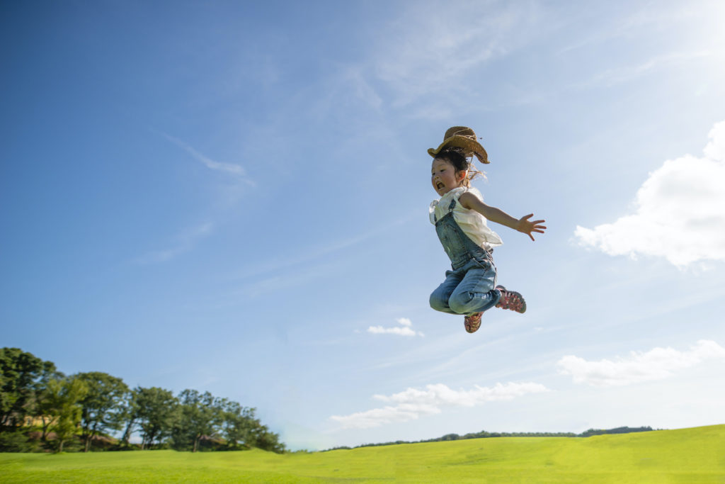 Girl jumping to the blue sky