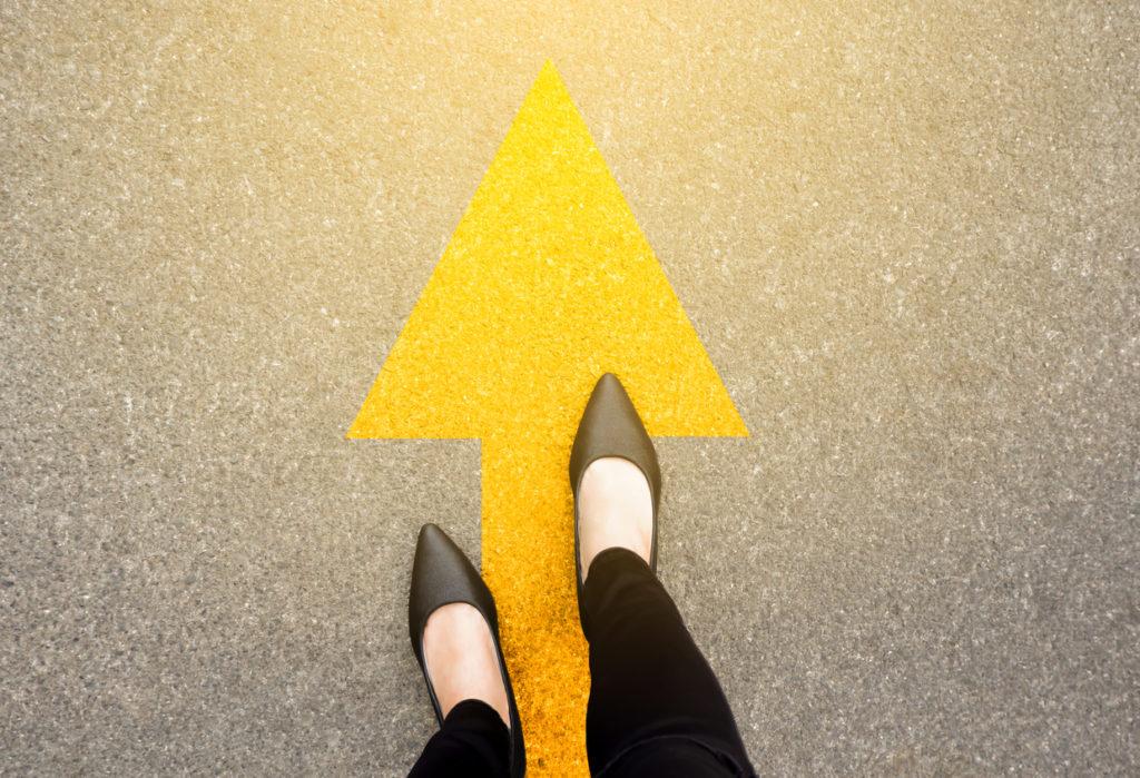 黄色い矢印を踏む黒い靴