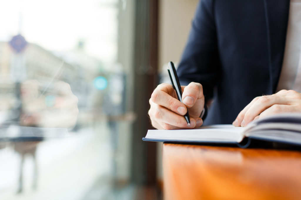 窓際のテーブルで紙に何かを書く様子